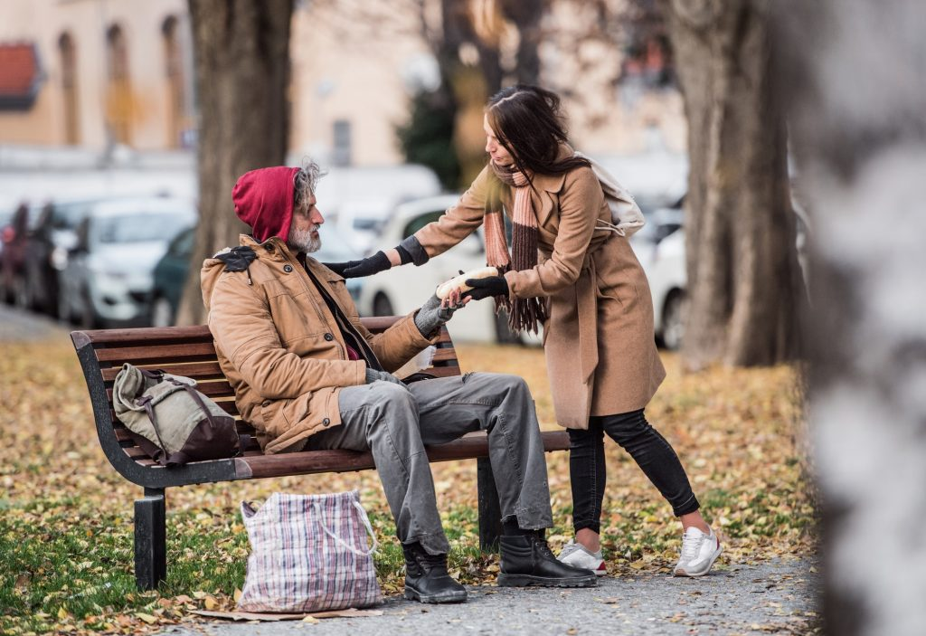 Young woman giving food to homeless man sitting on a bench in city.